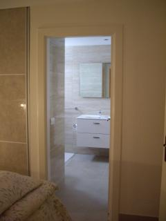 PS3 Bathroom off bedroom with large shower enclosure with hanging toilet and sink basin