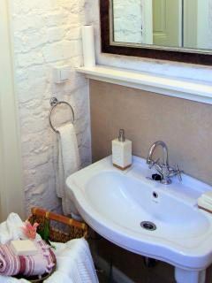 Bathroom with toilet, sink, shower, and heated towel rack