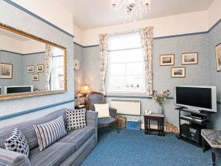 The comfortable living room has a wide screen TV and is open plan to dining area & kitchen.