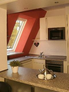The fitted kitchen with the hatch from the dining area.