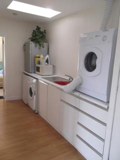 Utility room with washing / drying facilities and additional fridge and freezer.
