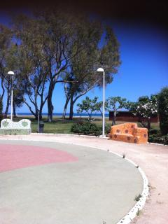 Car spaces, walking area and the beach.