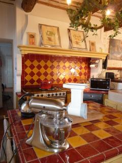 La cuisine avec son ilot central et son accès à la salle de bain du bas, la lingerie, jardin