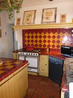 La cuisine avec sa gazinière de marque 'GODIN', son lave vaisselle et son four à micro ond