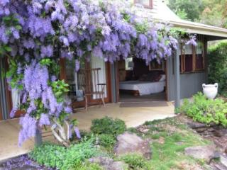 Main bedroom opens onto the back veranda with its wonderful Petria flowering vine, at French Cottage