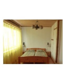 Schlafraum mit Doppelbett, Nachttischen, Nachttischlampen und Fachwerkwand