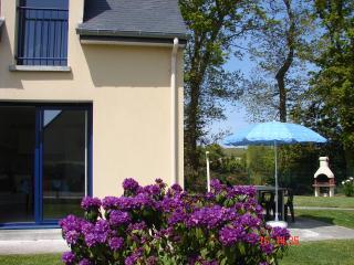 vue de face avec terrasse équipée de transats,barbecue et jardin fleuri clos d'environ 200 M2