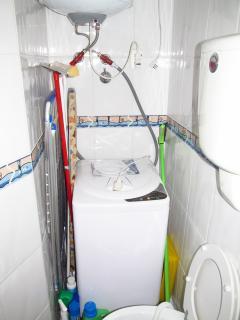 Toilette com lavarroupas, tábua de passar, ferro, e varal