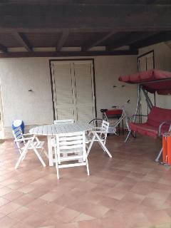 Veranda con tavolo, dondolo e sdraio per prendere il sole