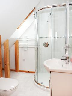 Master bathroom with large corner shower cubicle, vanity unit and long mirror with shaver socket