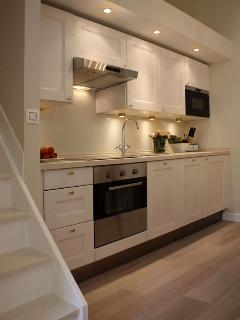 Fully fitted kitchen with bleached wood cabinets to complement the bleached oak parquet flooring