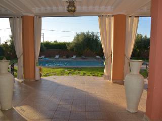 terrasse devant piscine avec salon à gauche et salle à manger à droite
