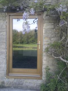 Door to the TV room and reflection of the large garden