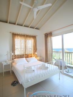 Master Bedroom with good cross ventilation, tall wooden ceilings and a Balcony overlooking the sea.