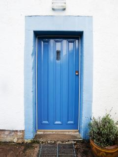 Rear door of Beckside Cottage, with outside lighting for summer evenings.