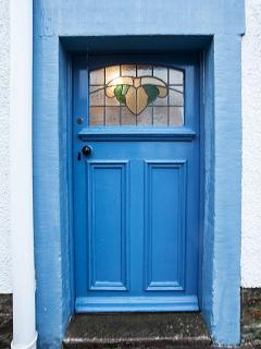 Front door with original stained glass window detailing head of a sheep