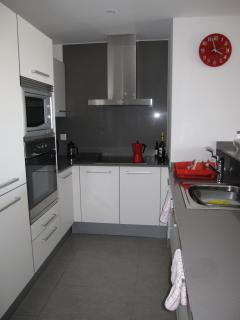 fully fitted kitchen with hob, cooker, microwave, fridge freezer and dishwasher