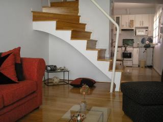 LIVING ROOM, THE STAIRS TO THE SECOND FLOOR AND PART OF THE KITCHEN