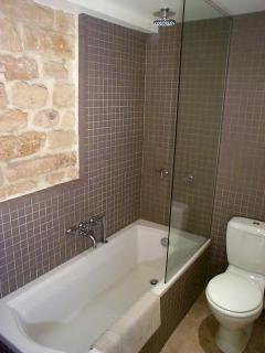 Large bathtub w/hand shower wand, and separate luxurious overhead shower.