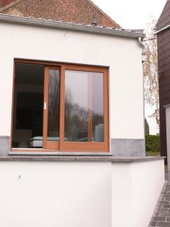 Salon avec baie vitrée et balcon éclairé.