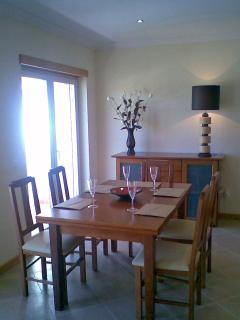 Dining area with double doors overlooking front of vill