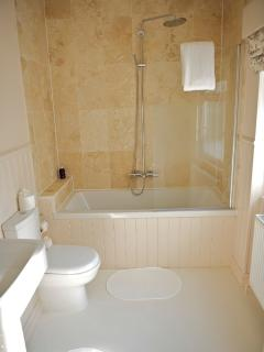 En-suite bathroom with limestone bath surround and rainfall shower (Stratford Suite)