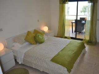 Master bedroom with en-suite bathroom, kingsize bed and balcony overlooking the pool