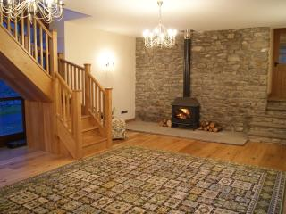 Spacious Hallway with Log Burner, Comfortable Seating & Oak Staircase