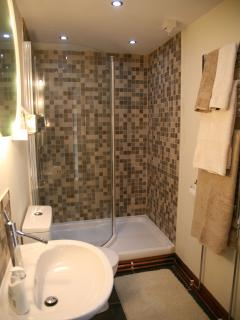 Large walk in shower with heated towel rail with soft fluffy towels provided.