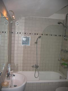 Bathroom with shower over bath, toilet and bidet