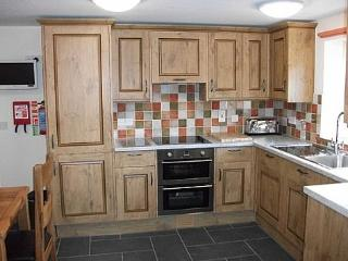 Fully equipped kitchen with country style oak furniture and TV