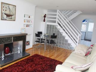 view from the lounge of the dining area and stairs to second floor. Archway leads to kitchen