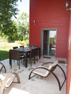 La terrasse principale avec grande table et fauteuils de repos