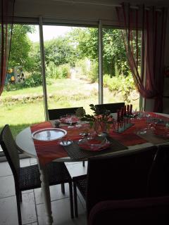 Le coin repas avec vue sur le jardin et ses grandes baies vitrées