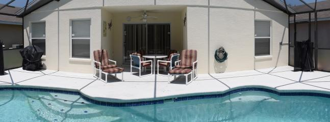 View of the pool and extended pool deck from the spa with seating area ideal for those long evenings
