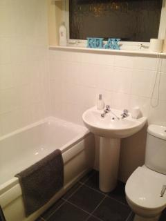 Modern white bathroom suite with over bath shower and tiled floor