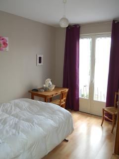 chambre avec un lit double, une armoire et un balcon