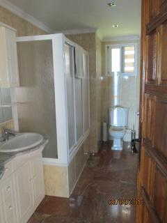 Large marble floored Family Bathroom. His and Hers sinks. Shower and bath . Hair dryer provided.