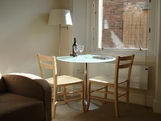 The dining room table can easily seat four guests by using the folding wooden chairs in the cupboard