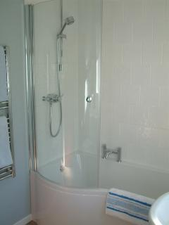 Bathroom with showerbath, heated towel rail, and contemporary fittings.