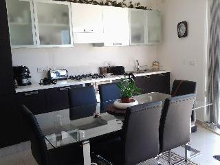Kitchen and dining area seating 6 people . Glass table and leather chairs