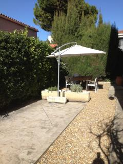 Garden area for apartment with dining table, parasol and BBQ