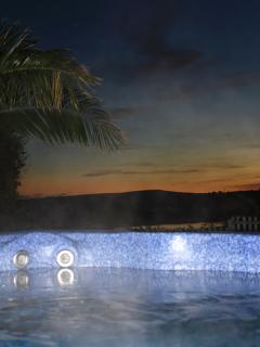 River Cottage hot tub at sunset overlooking the water and Tennyson Downs