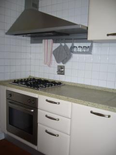 cucina attrezzata con piano cottura, forno, frigo, lavastoviglie e lavatrice