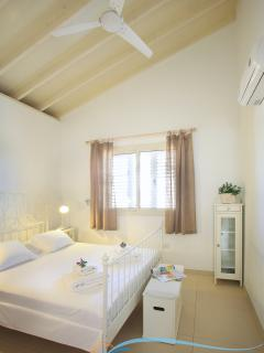 Second bedroom with double bed. Tall wooden ceilings and off white tones, good ventilation.