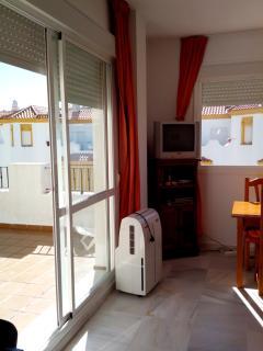 Salón con salida a la terraza y ventana a la calle