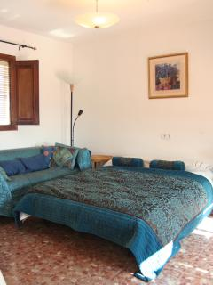 Double bedroom with patio doors opening onto terrace which looks over the village and the sierra