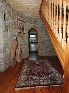 The hand built wooden doors and stairway with local stone walls in the entrance area