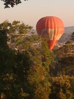 hot air balloon flying over the house