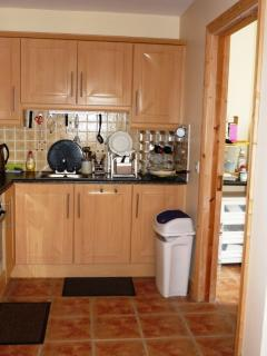 Kitchen area with utility room through a door on the right